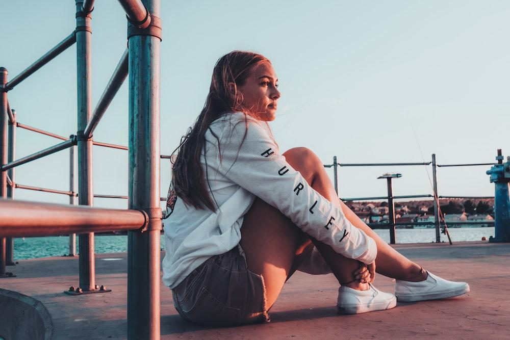 woman sits on ground near sea