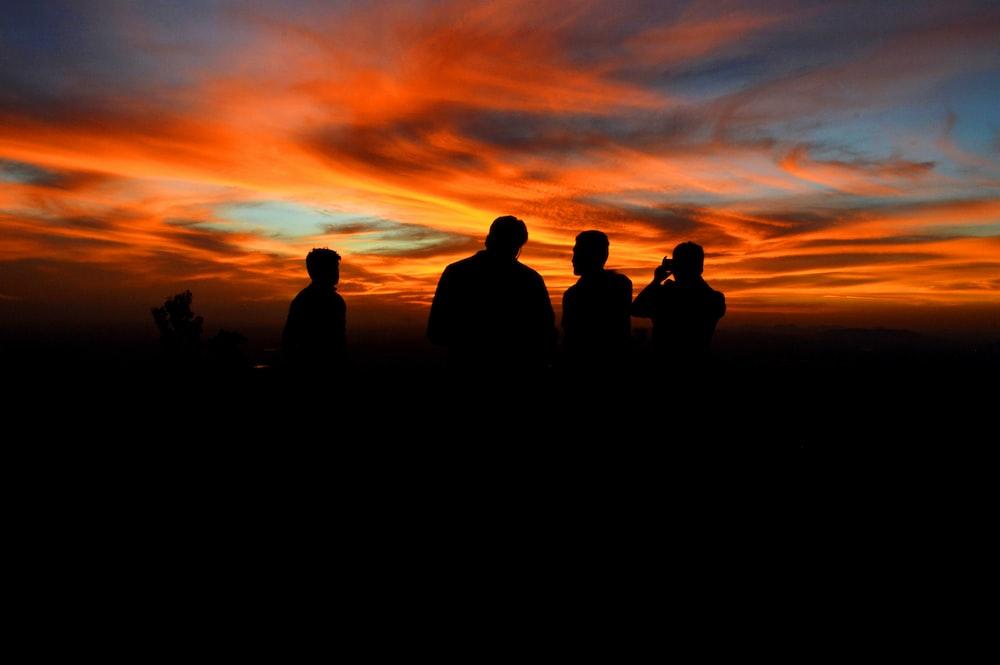 silhouette of four person under orange sky