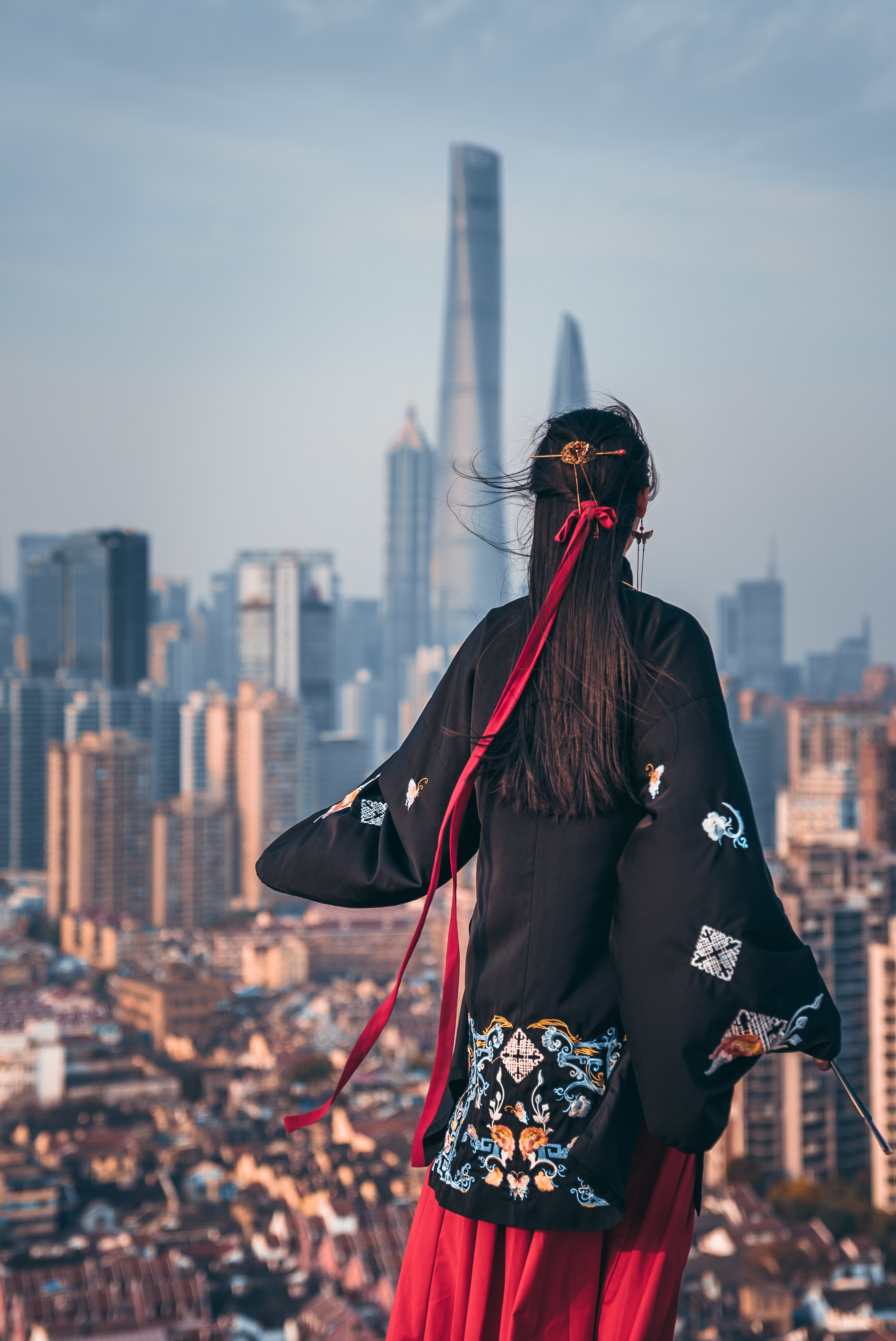 black haired woman in black coat staring at building during daytime