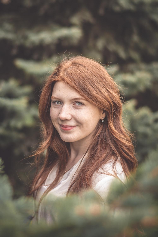 woman wearing white crew-neck shirt behind trees during daytime