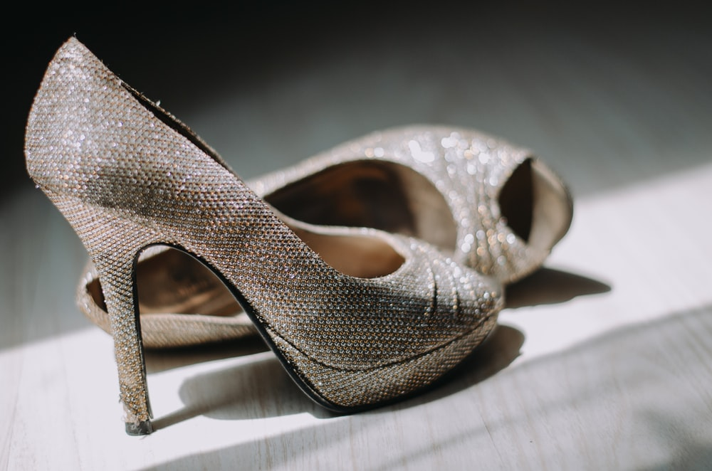 close up photography of pair of silver leather platform stilettos