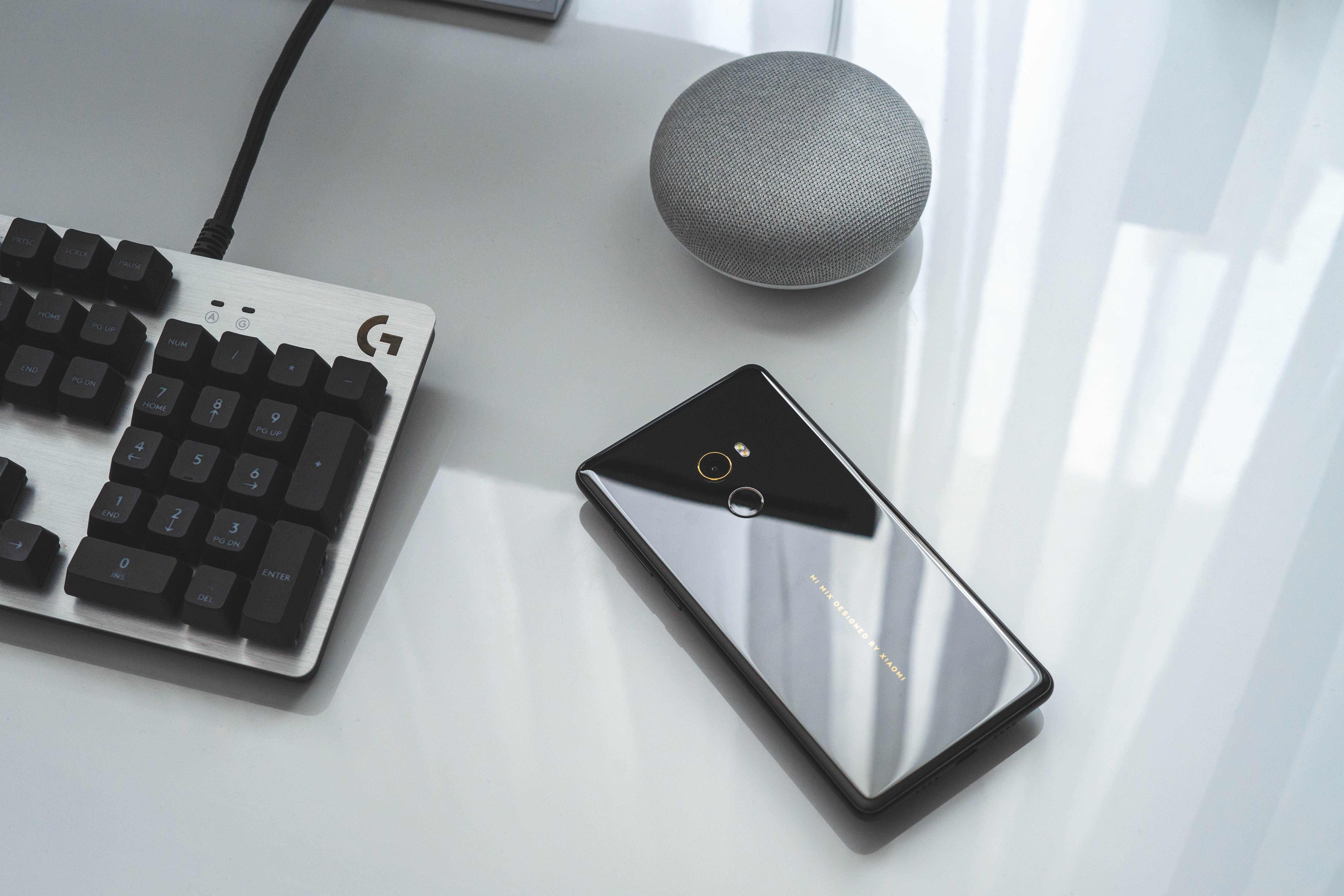 black Android smartphone near computer keyboard