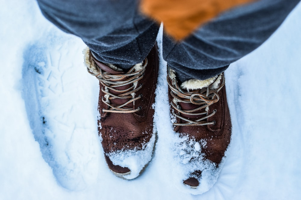 person standing wearing brown boots on snow
