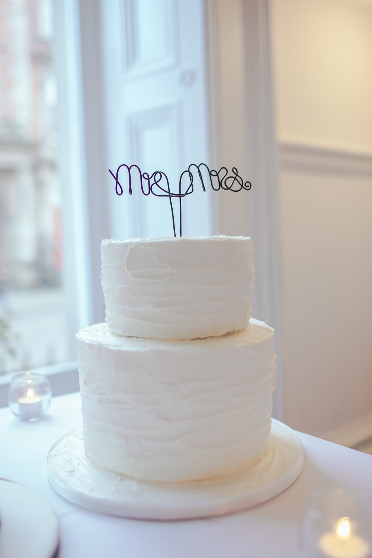 white 2-tier cake on white wooden table