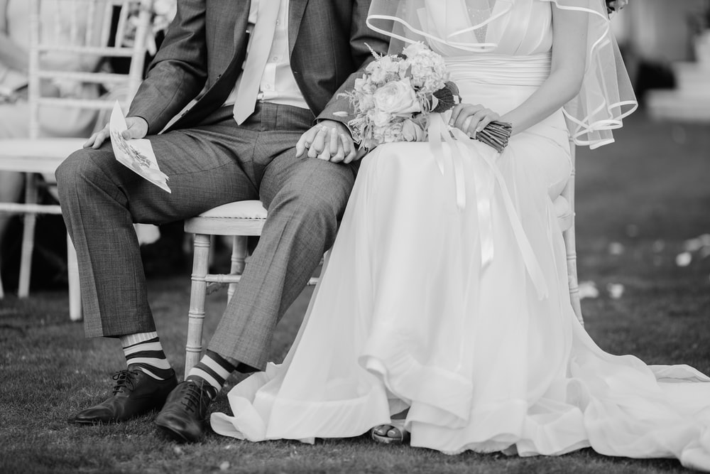 greyscale photography of groom and bride sitting on chairs