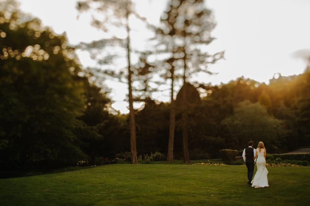 couple walking near tree during daytime