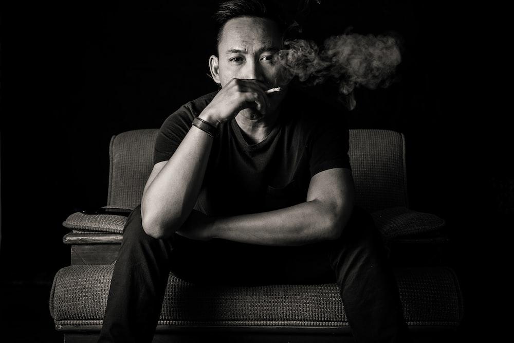 grayscale photo of sitting man smoking a cigarette