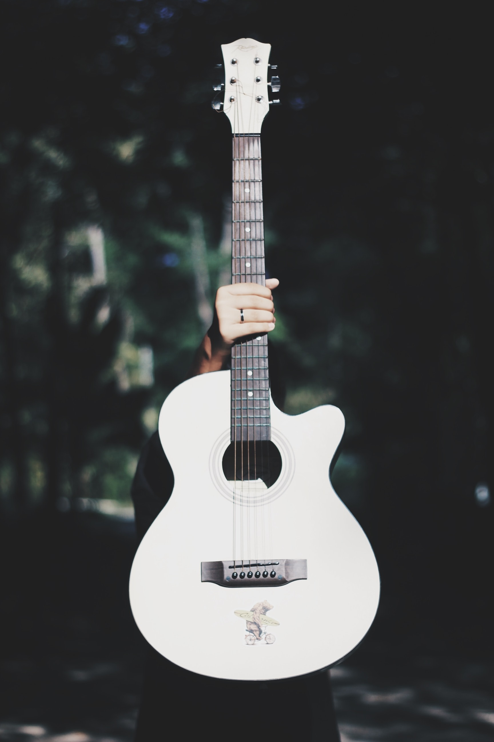 person holding white acoustic guitar