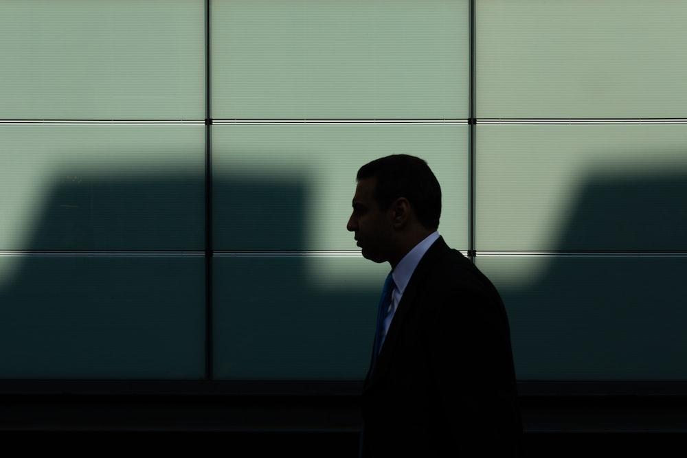 man walking near gray concrete wall