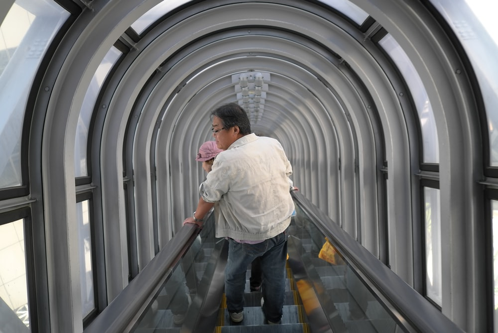 man holding baby riding escalator