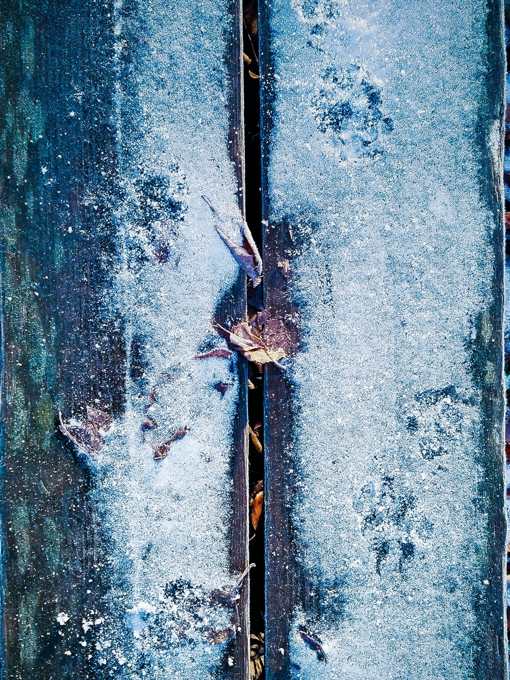 green wooden plank board covered of snow
