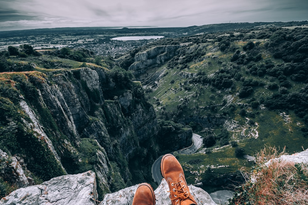 person wearing brown boots on top of mountain