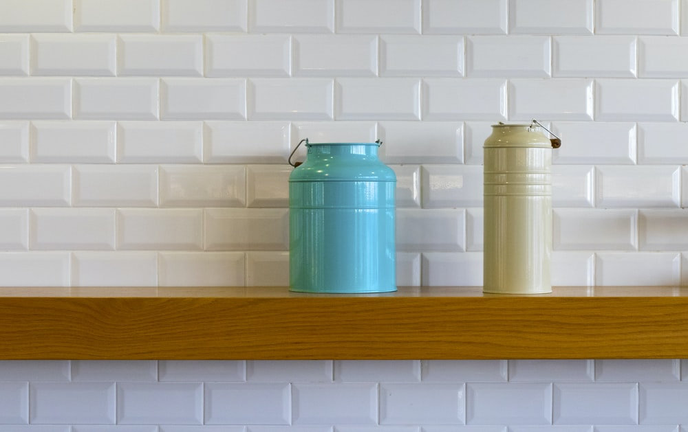 two teal and brown metal cans on shelf