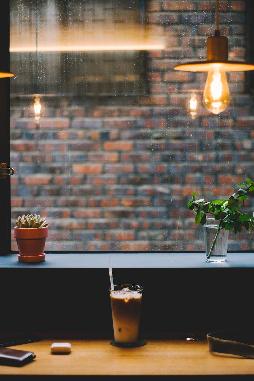 clear drinking glass beside wall