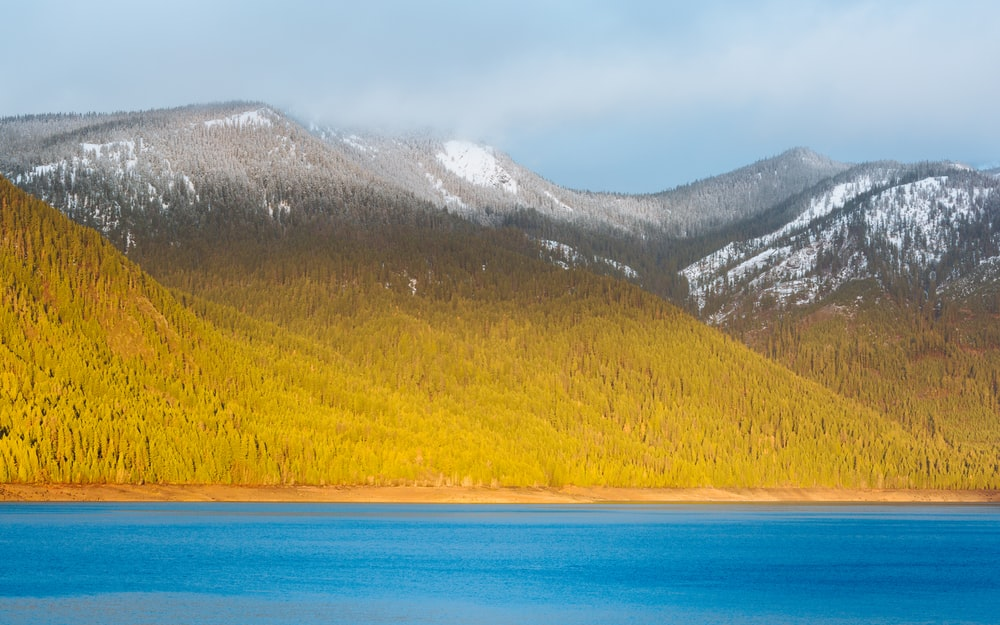 blue body of water near mountain during daytime