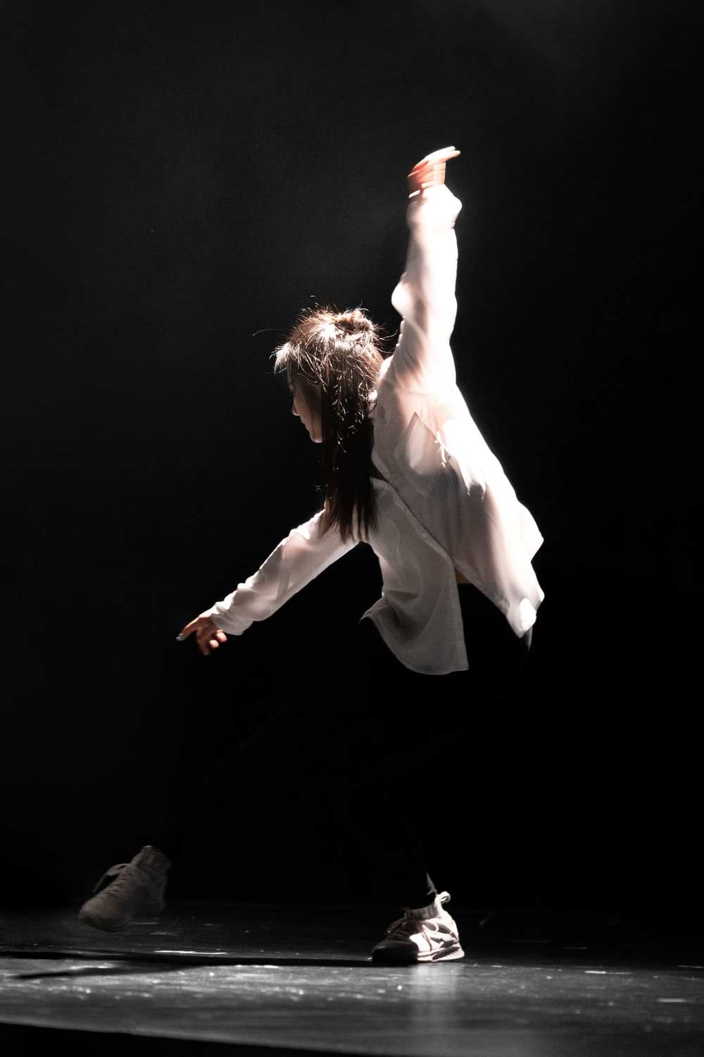 woman in white dress shirt dancing on stage