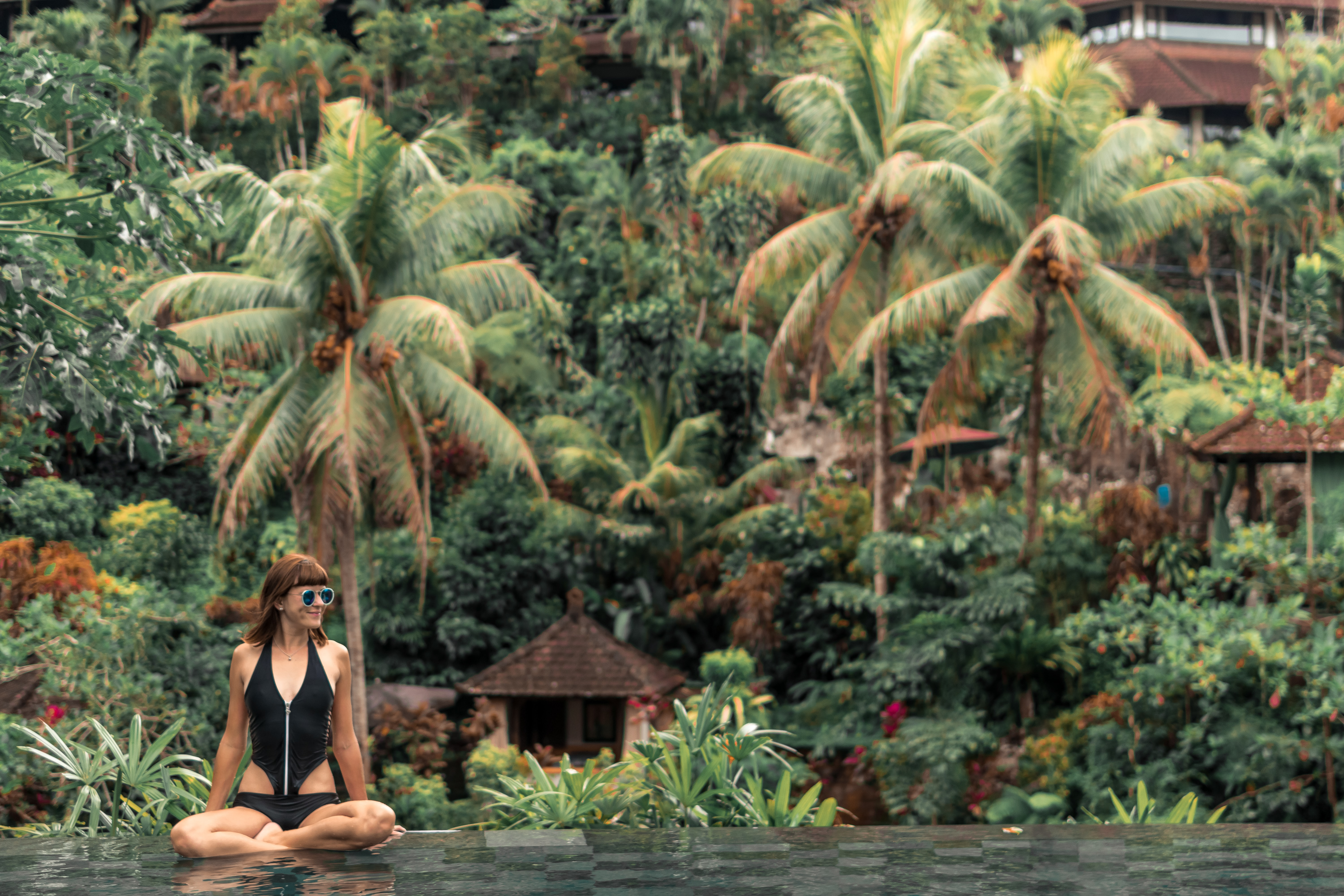 woman in black swimsuit sitting near green palm tree during daytime