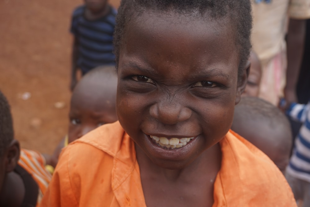 smiling boy in orange collar top during daytime