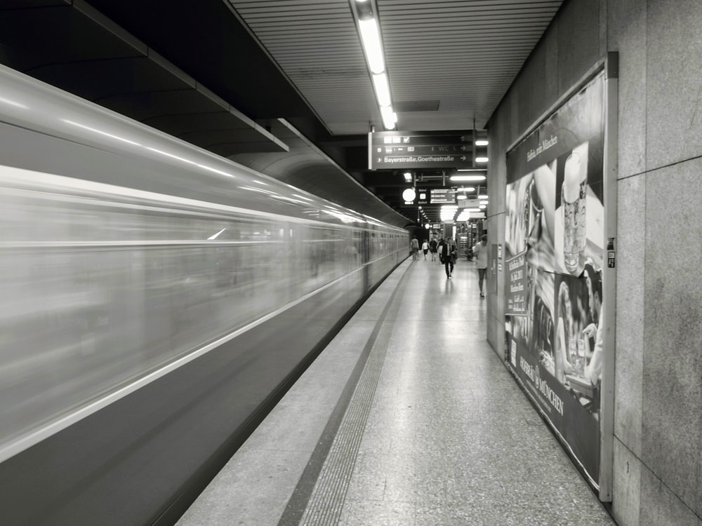 grayscale photo of people standing near train