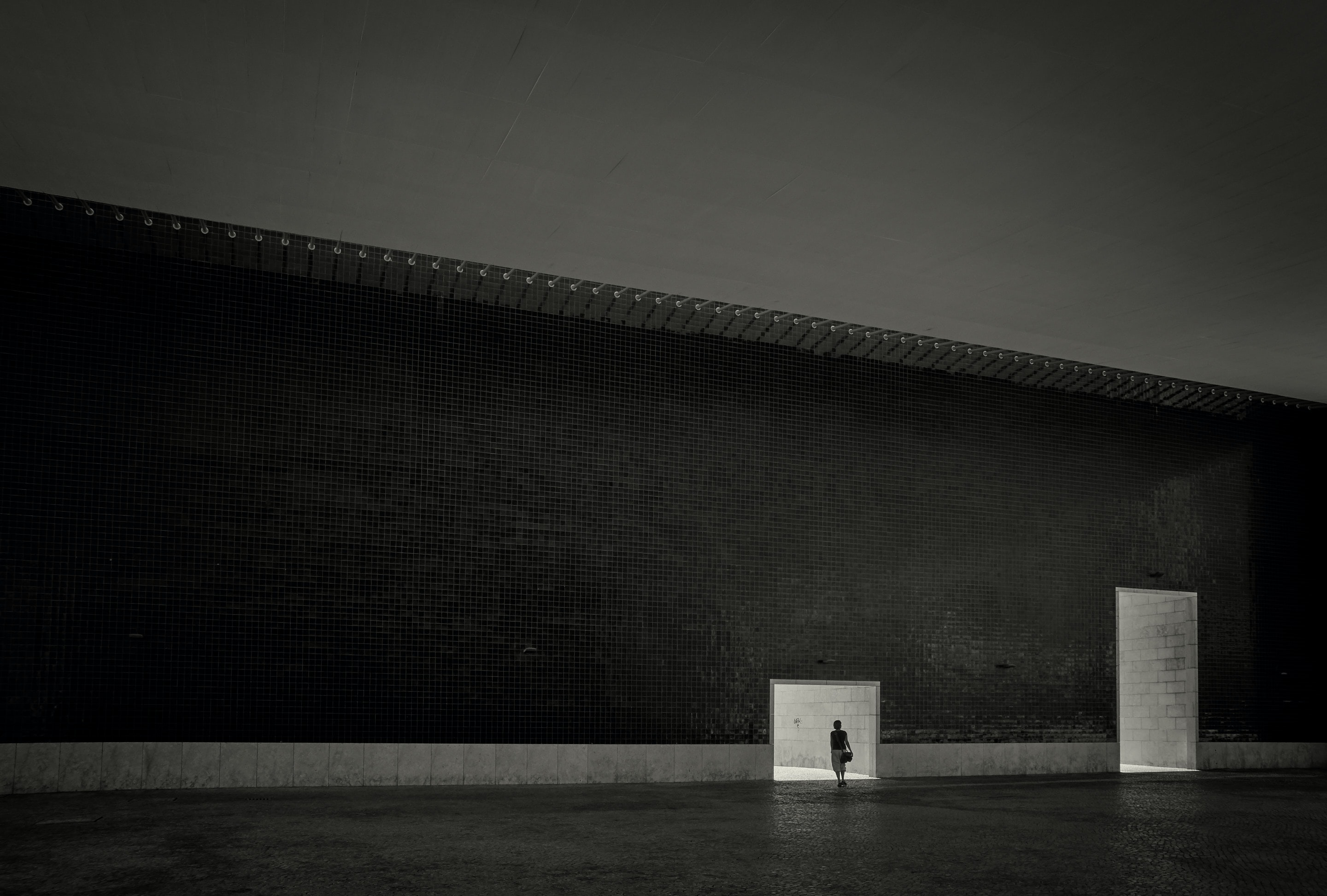 person standing in front of small tunnel beside of big tunnel grayscale photography