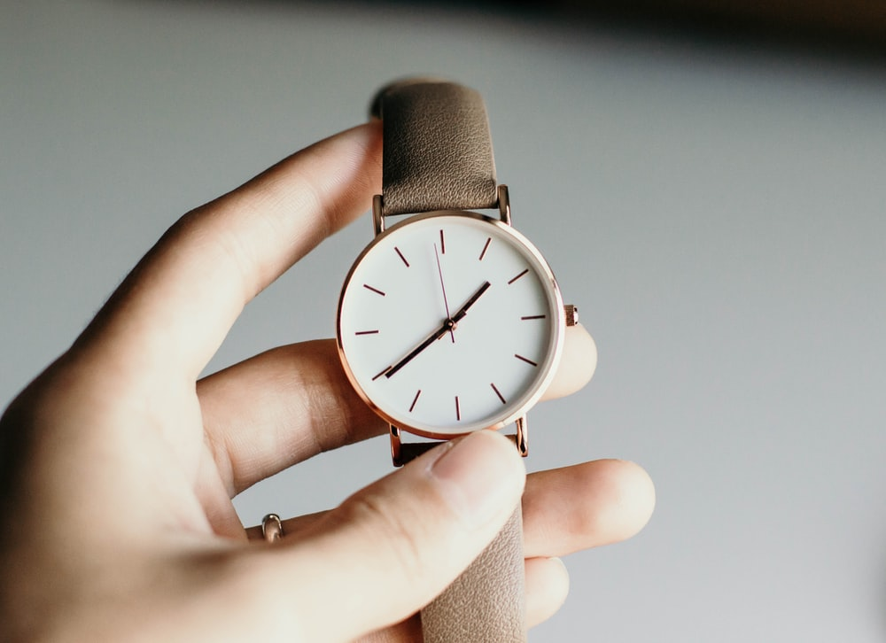 person holding analog watch