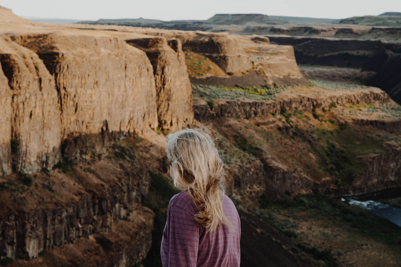 woman standing near brown mountain under blue sky