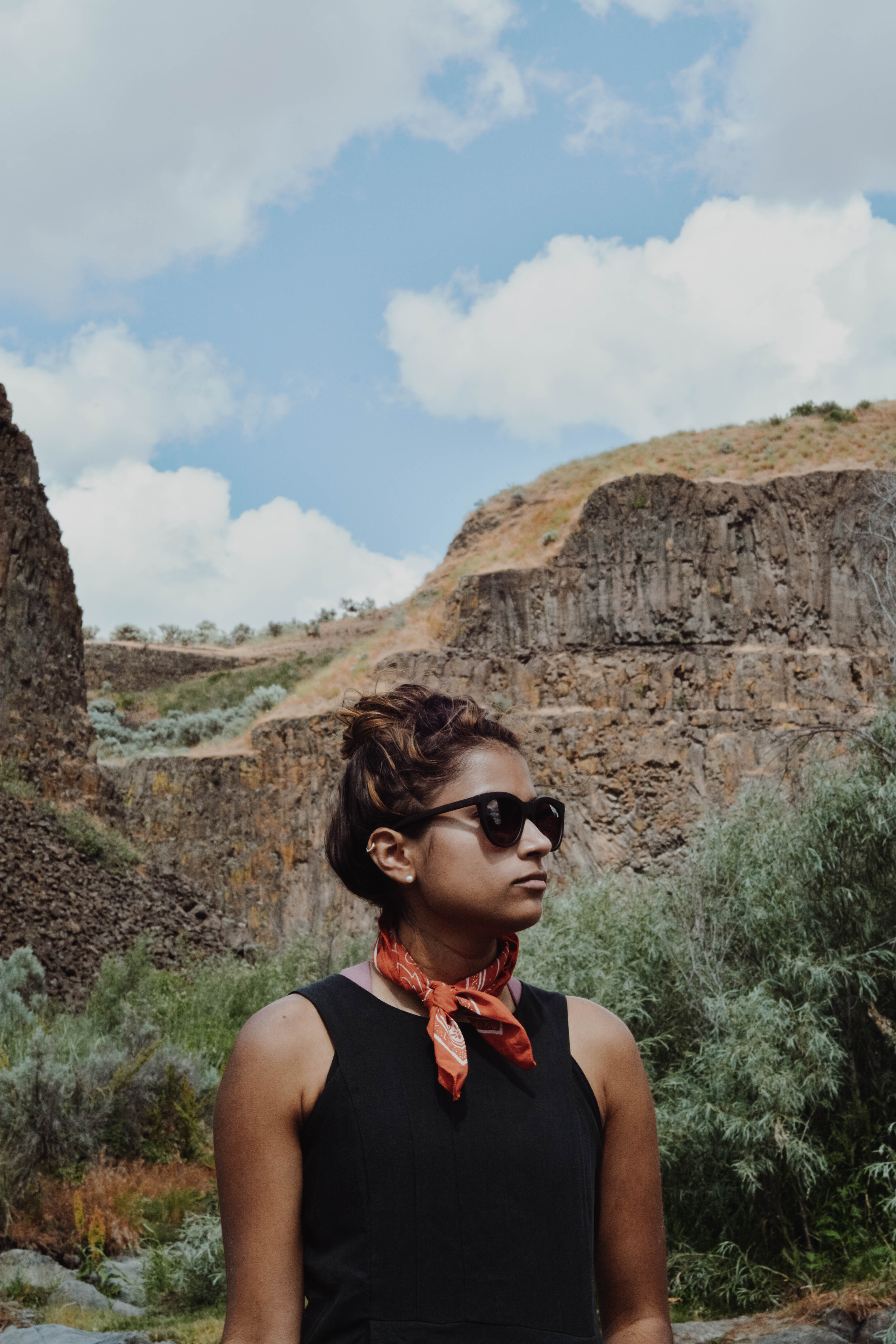 woman wearing black tank top stands beside brown cliff under blue sky during daytime