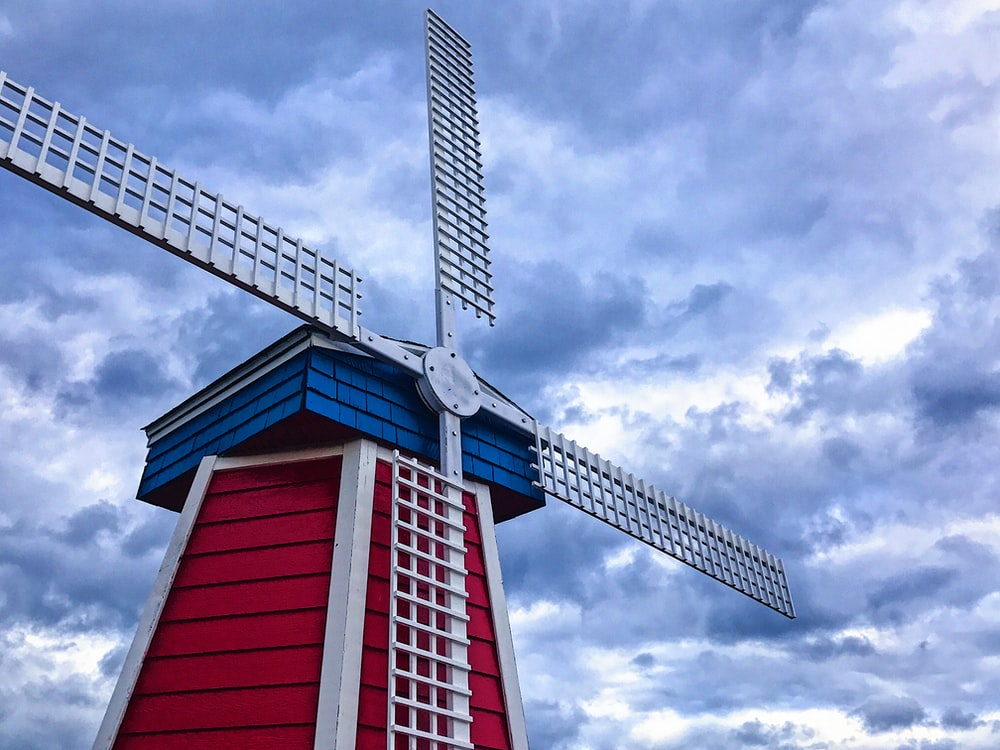 white and red barn house with wind mill