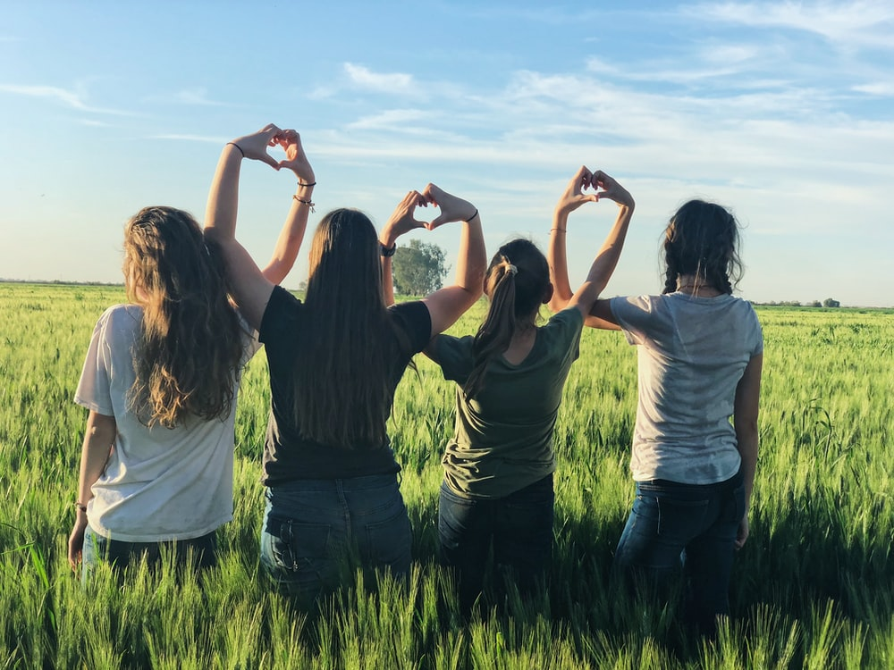 women forming heart gestures during daytime
