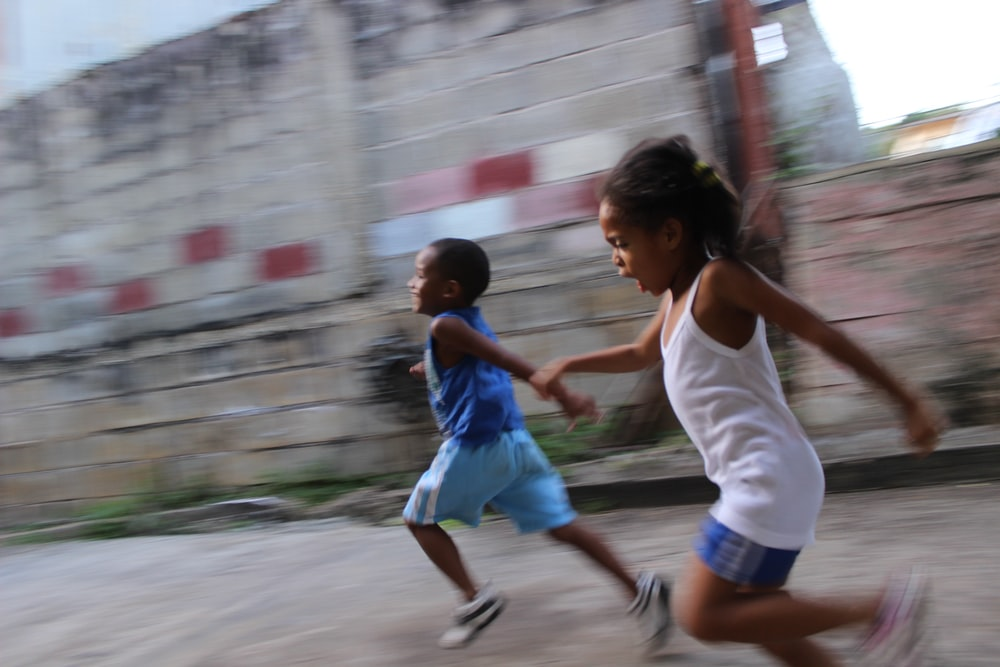 two girl and boy running beside gray wall