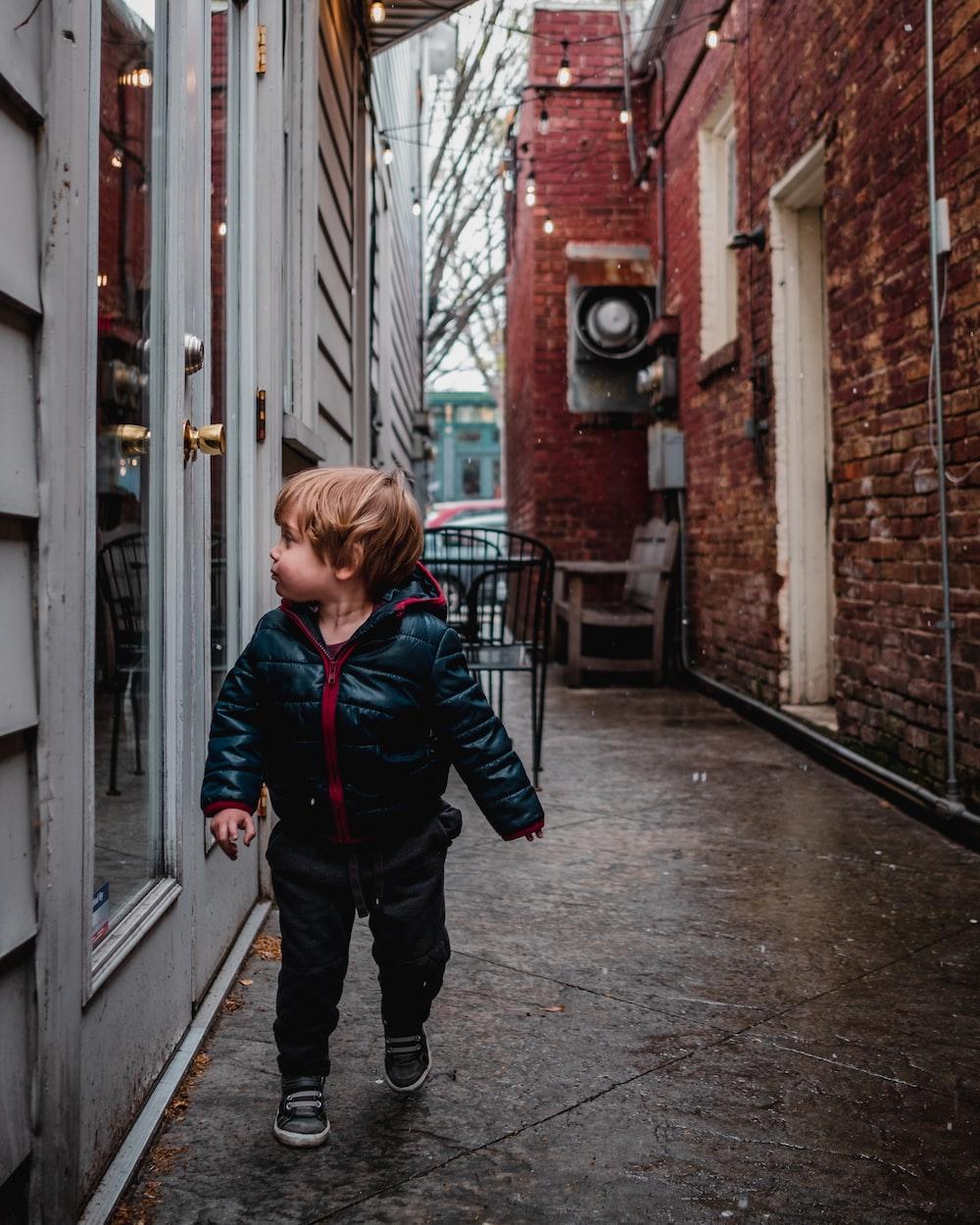 boy in black jacket walking looking at full-glass door