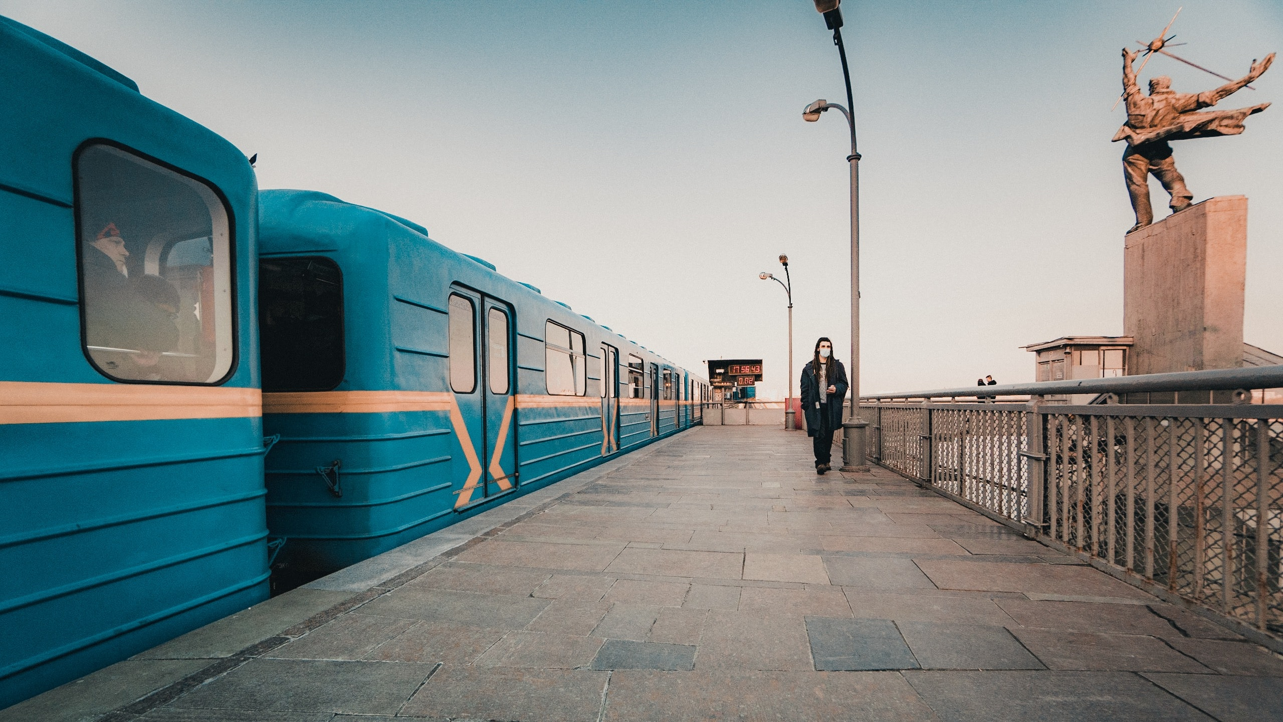 person walking near blue train during daytime