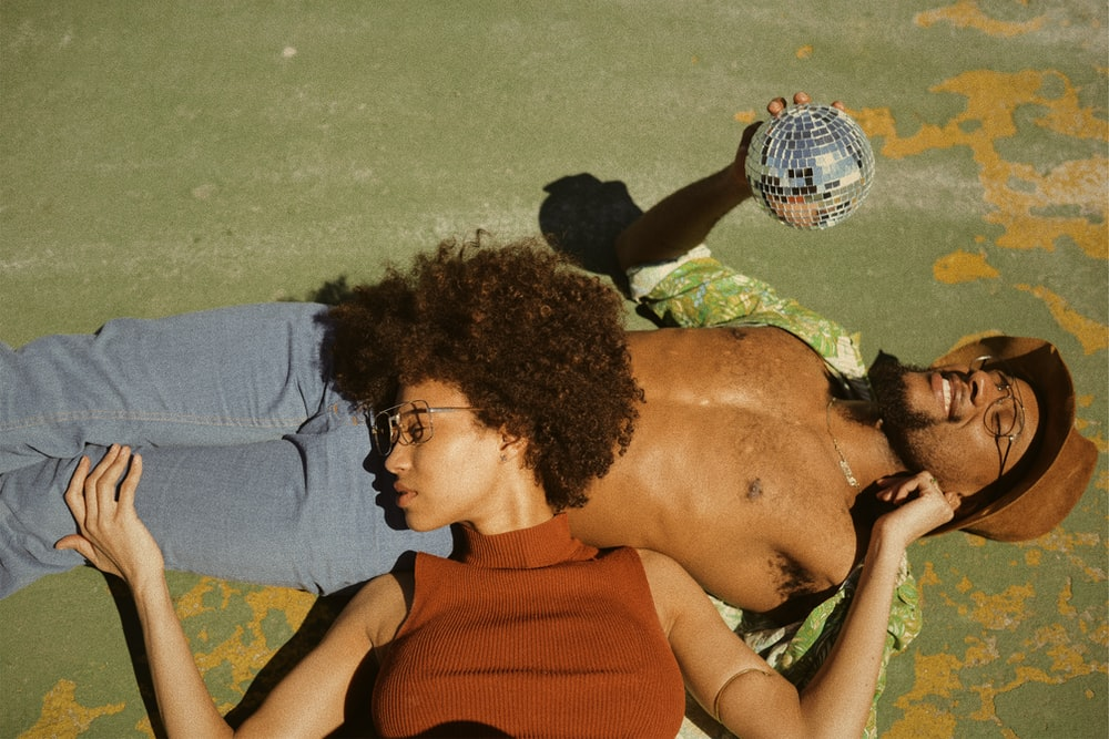 woman in brown turtleneck sleeveless top lying on man's stomach wearing green button-up collared shirt holding disco ball