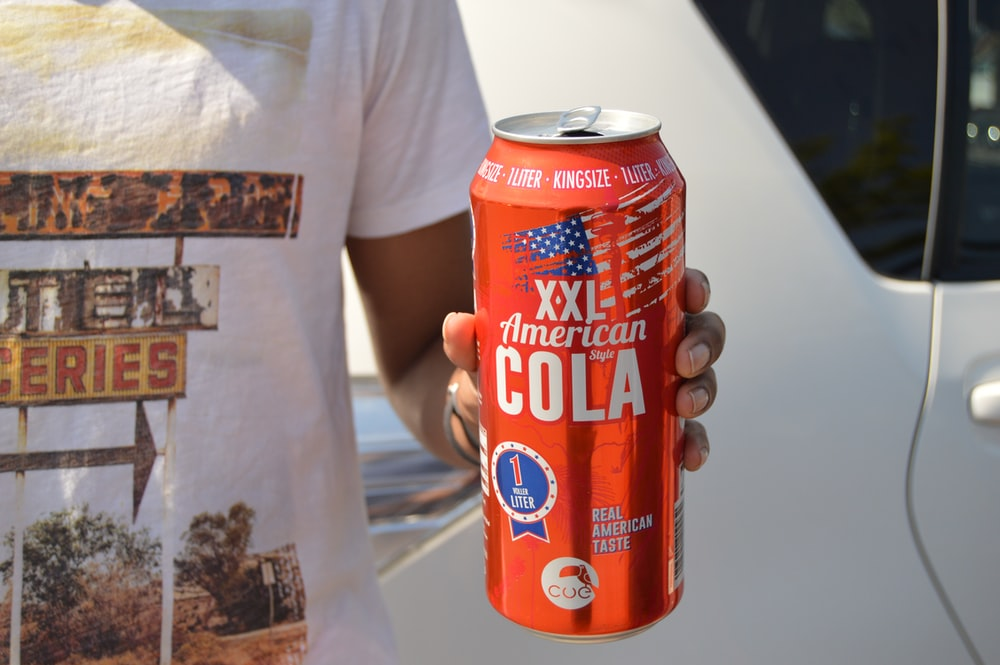 person holding American Cola tin can