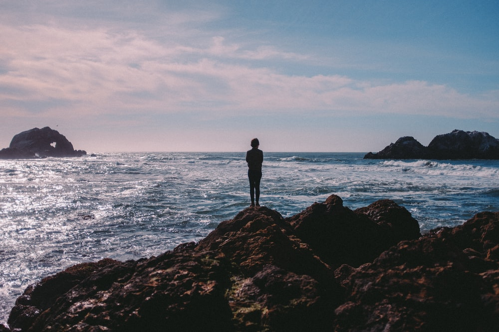person standing on coastal rock facing ocean at daytime