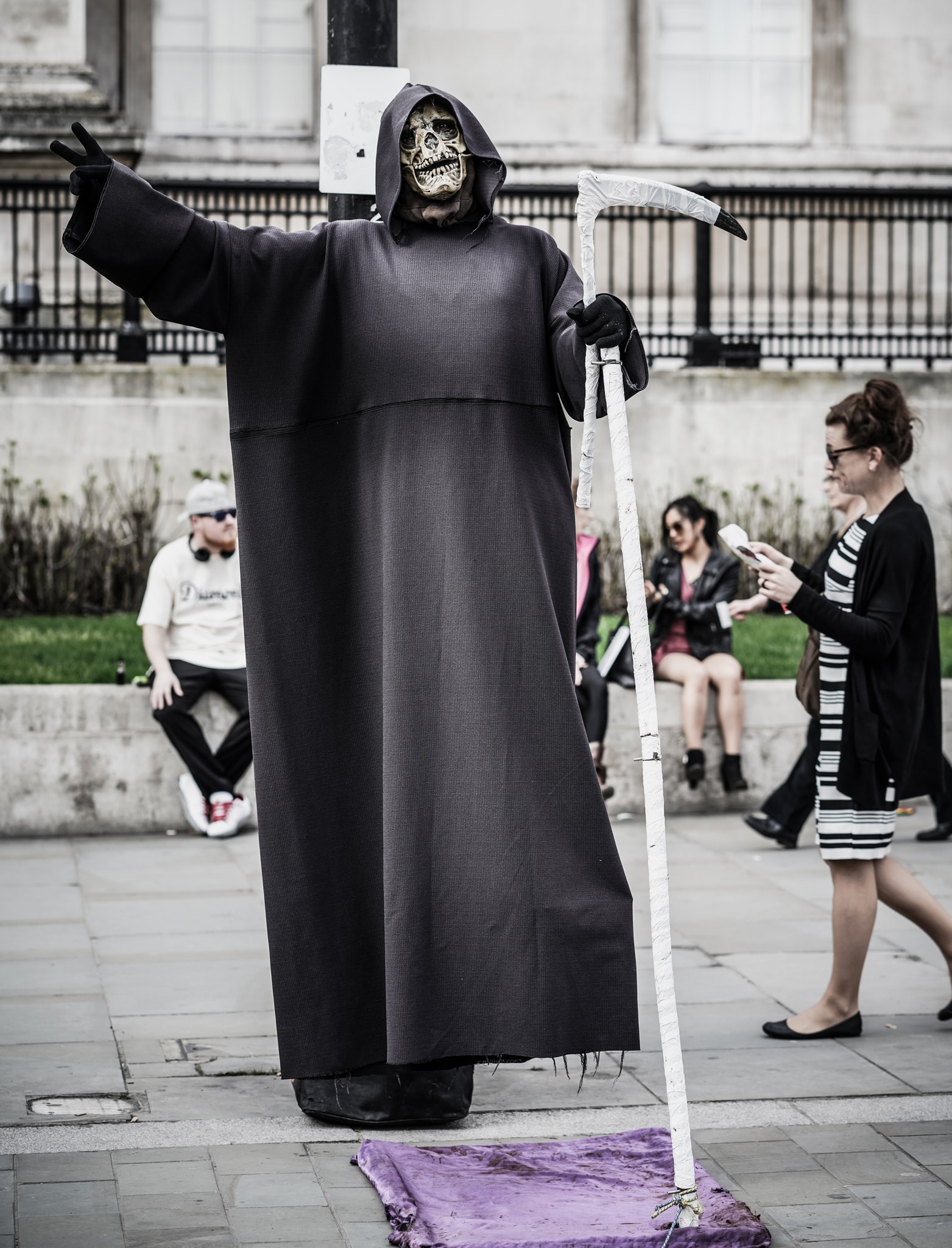 man in grim reaper costume with scythe near woman walking and people sitting on ledge