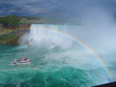 white and black fishing boat in blue ocean water under rainbow during daytime niagara falls zoom background