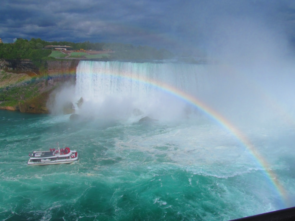white and black fishing boat in blue ocean water under rainbow during daytime