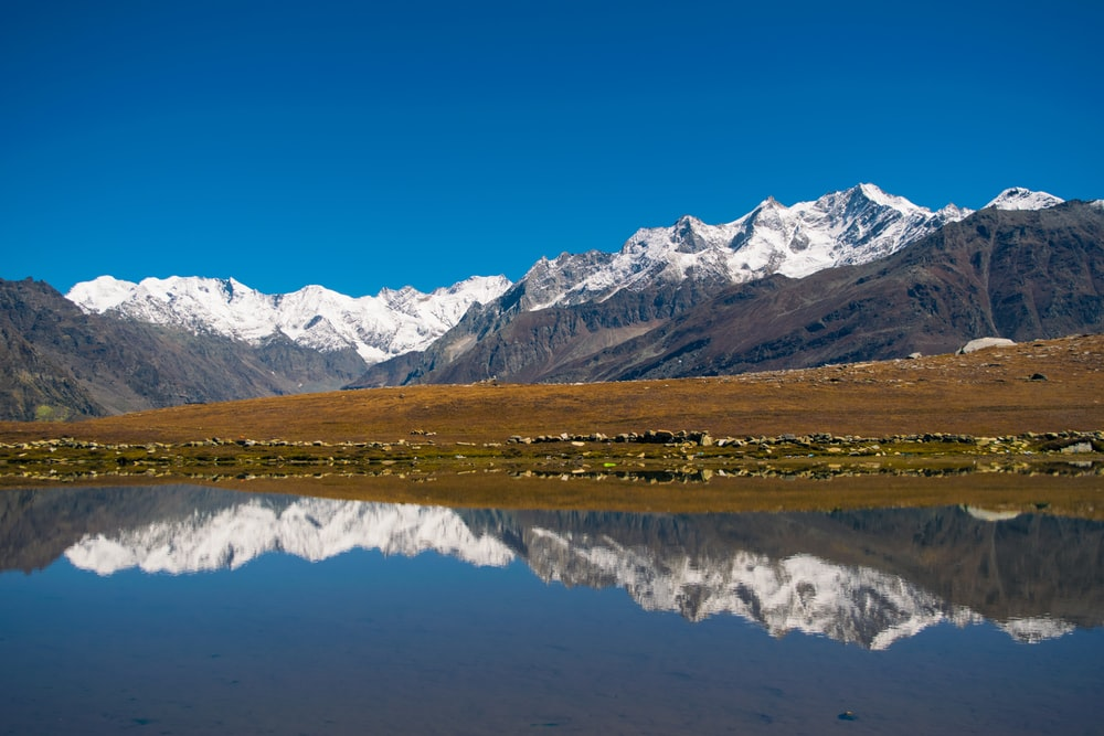 panoramic photographic of mountain reflecting on body of water