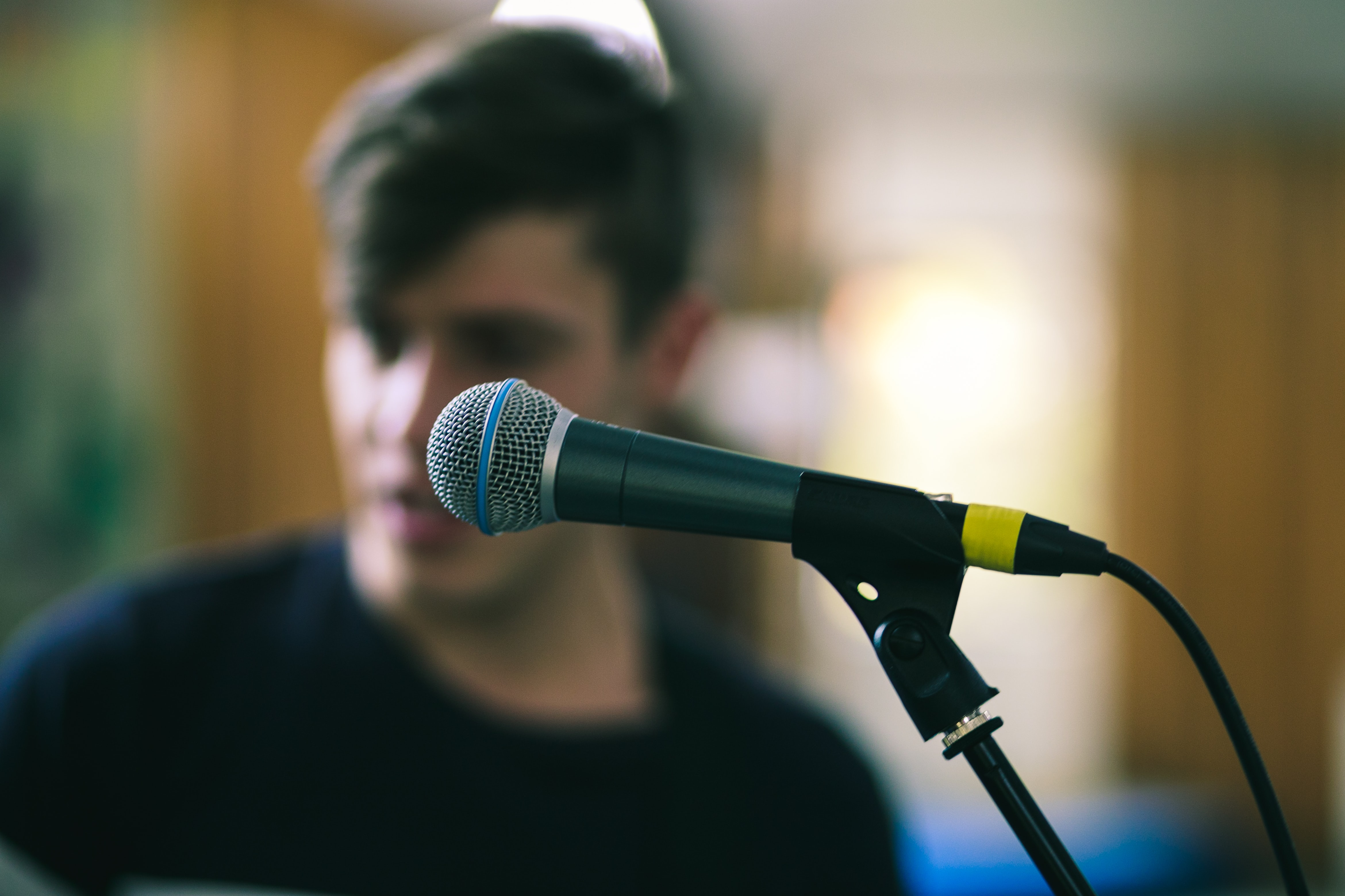 selective focus photography of black corded microphone on stand