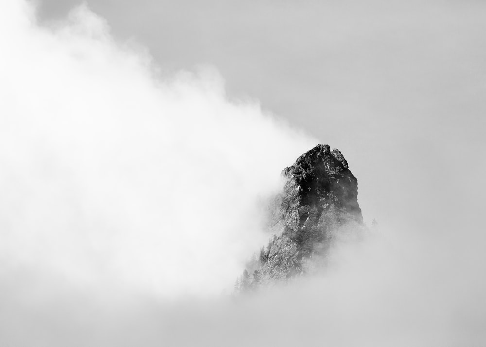 mountain covered with clouds grayscale photography