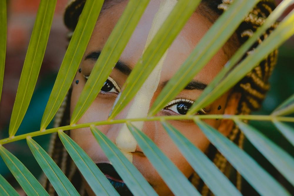 woman behind green leaf plant