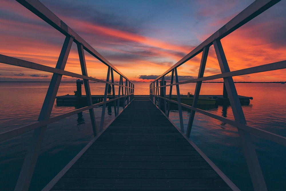 brown and white wooden sea dock at sunset