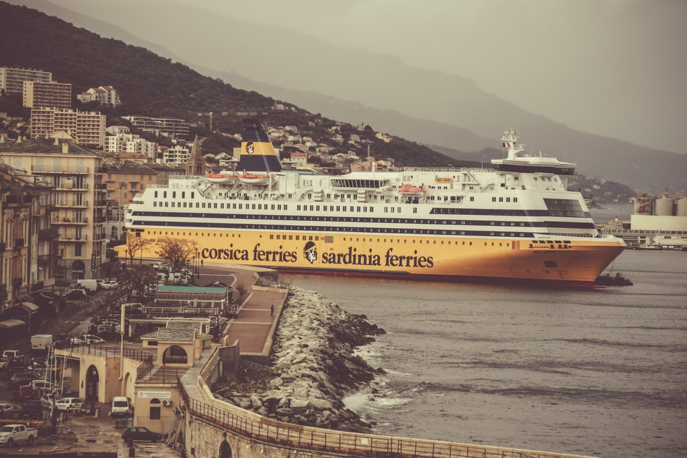 yellow and white cruise ship on body of water