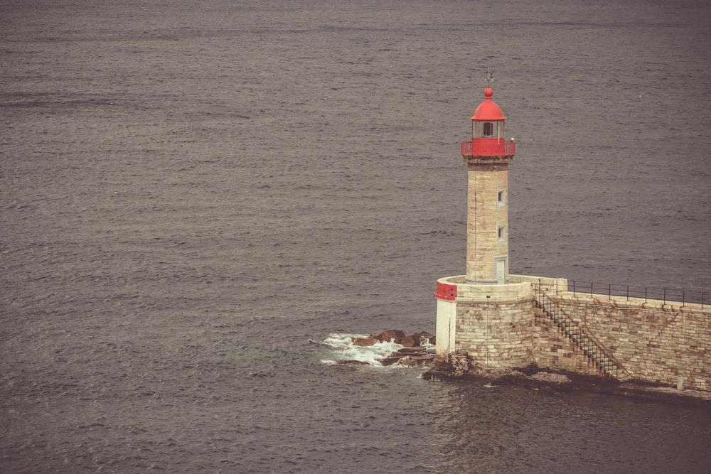 white lighthouse near ocean water during daytime