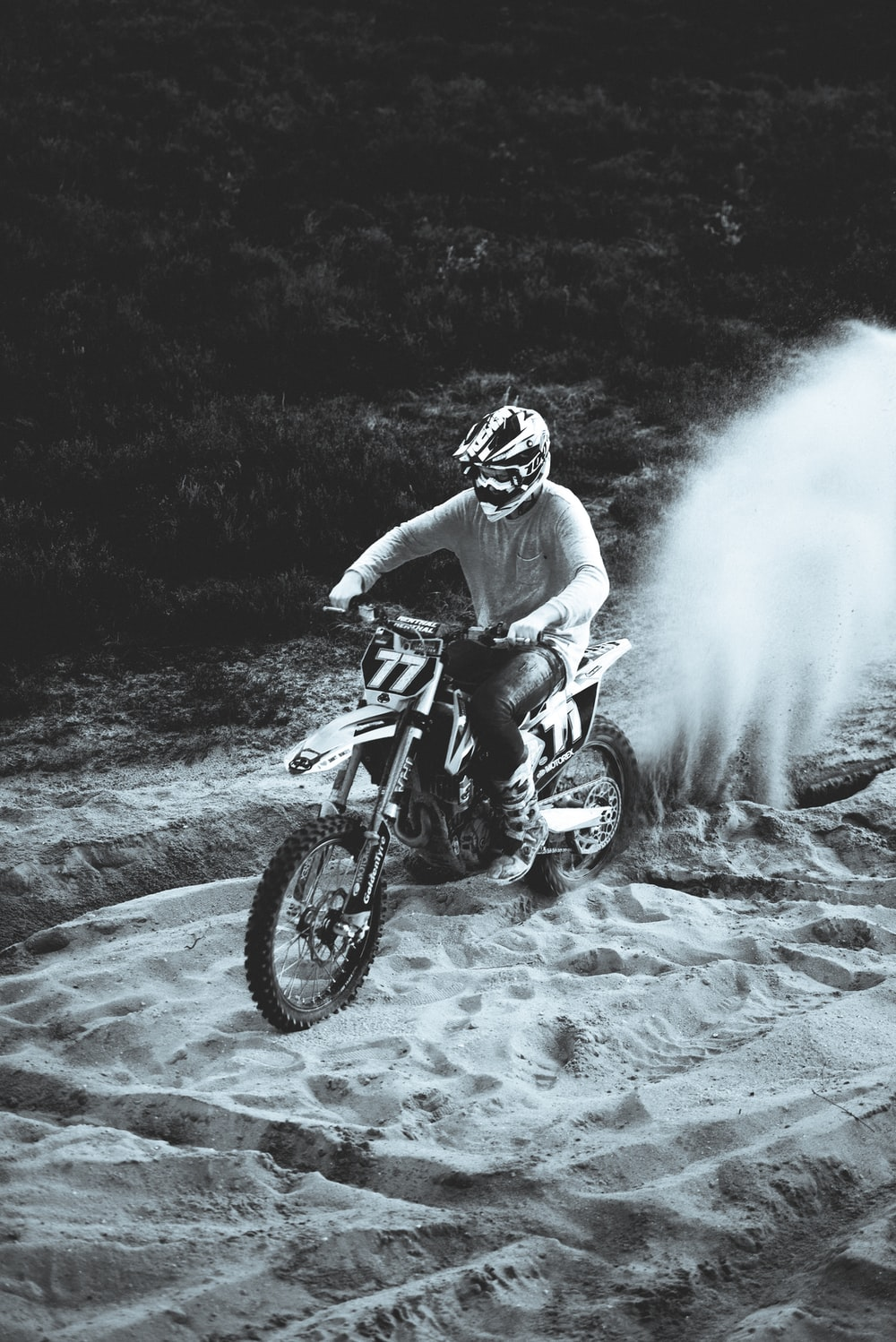 grayscale photography of man ride on dirt bike