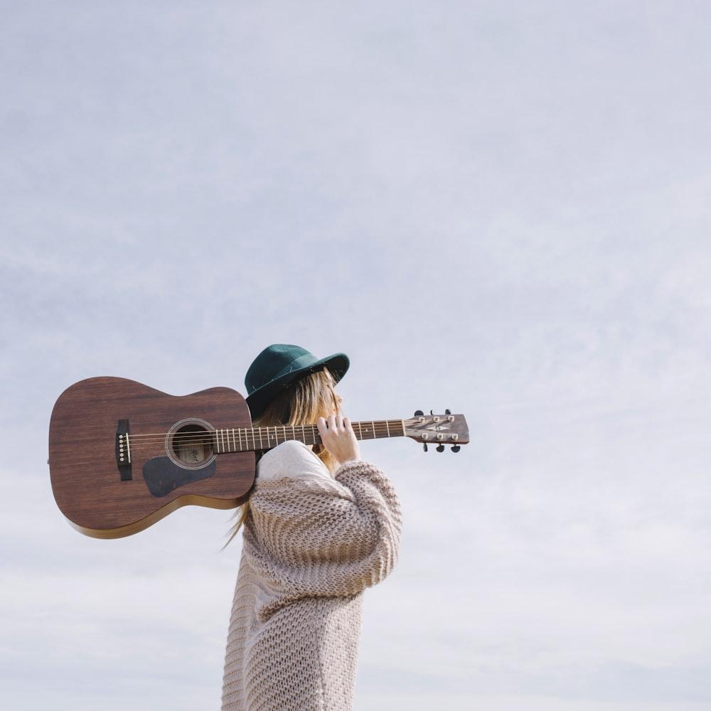 woman carrying brown acoustic guitar