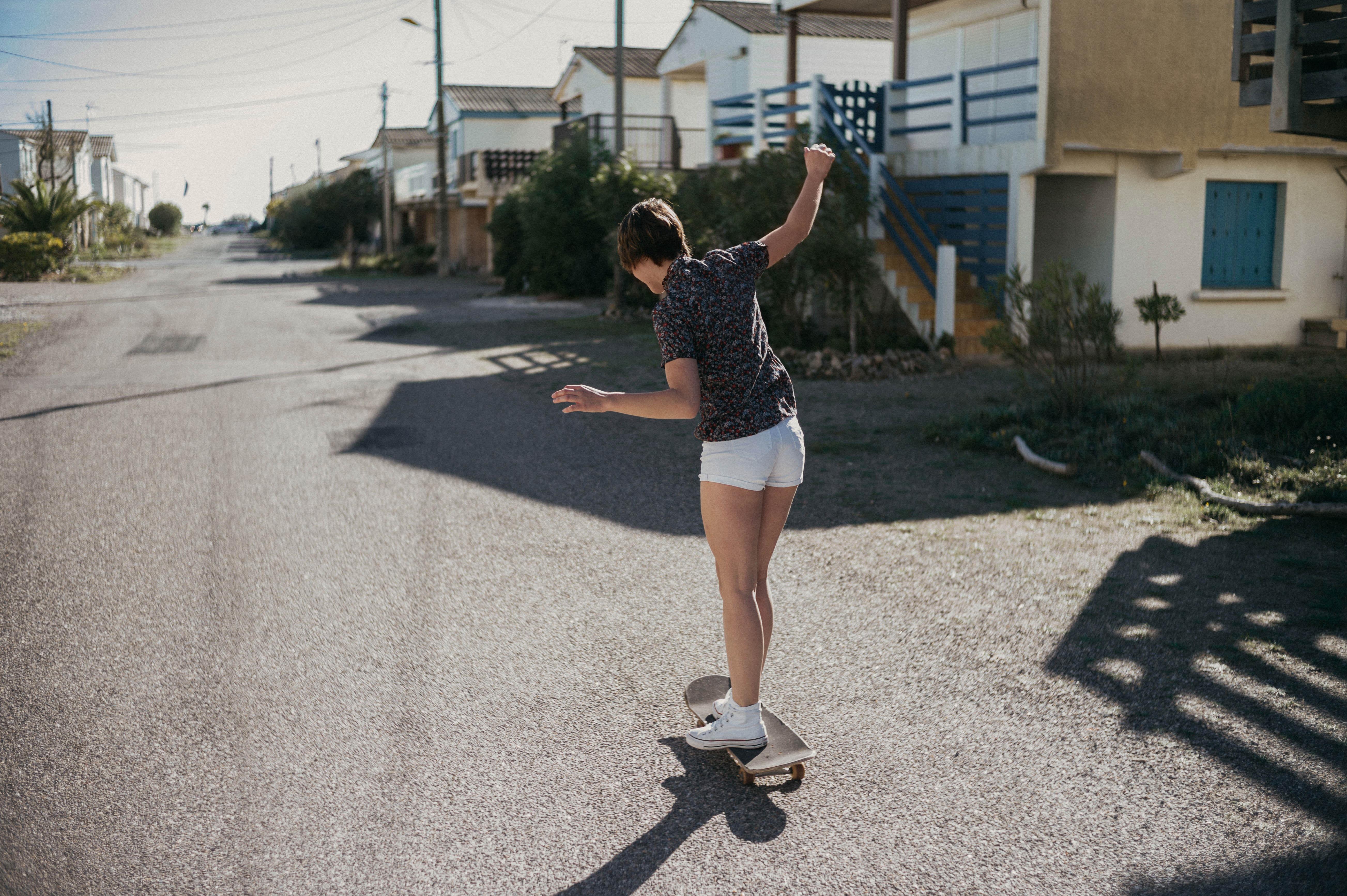 woman riding on skateboard near on houses