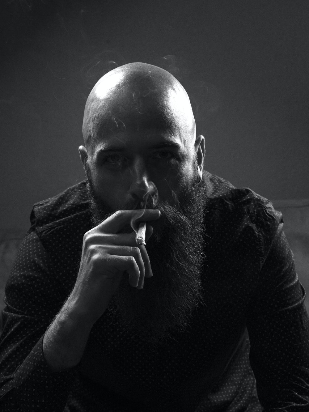 grayscale photo of man smoking cigarette