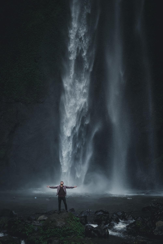 man in gray jacket standing near waterfalls